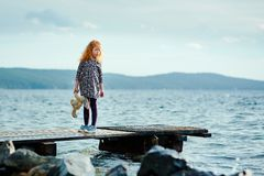 Free A Lonely Girl With A Plush Bunny Is Standing On The Pier And Loo Royalty Free Stock Images - 119388829