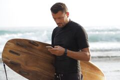 Free A Male Surfer Holds A Brown Surfboard And Uses A Smartphone Stock Photography - 217925092