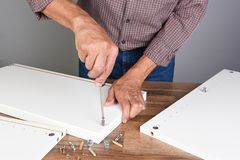 A Man Assembling A DIY Piece Of Furniture. Person Is Using A Screwdriver Inserting A Piece Of Hardware Royalty Free Stock Image