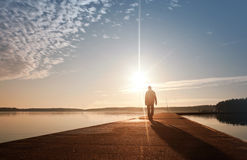 A Man Goes On The Pier In The Sunrise Royalty Free Stock Image