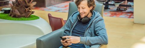 Free A Man In The Lounge Area At The Airport Is Waiting For His Plane, Uses A Smartphone And Headphones. Young Smiling Man Royalty Free Stock Image - 139226096