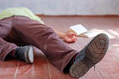 A Man Is Lying On A Dirty Floor In A Room Next To An Open Book Royalty Free Stock Photos