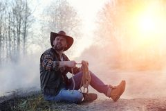 A Man Is Wearing A Cowboy Hat And A Loso In The Field. American Stock Image