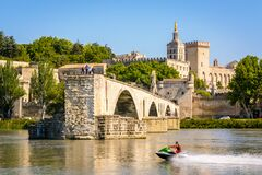 Free A Man Jet Skiing On The Rhone River In Front Of The Saint-Benezet Bridge And The Papal Palace In Avignon, France Stock Photography - 182560632