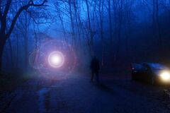 Free A Man Next To A Car Looking At A Glowing UFO, Floating Above A Track In A Spooky Misty Forest, Science Fiction Concept Stock Images - 182601484