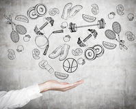 A Man S Hand In Formal Shirt Offers A Range Of Sport Activities And Sport Equipment. Sport Icons Are Drawn On The Concrete Wall. A Royalty Free Stock Image