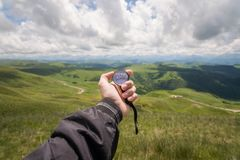 Free A Man`s Hand Of A Tourist With An Authentic Compass On The Background Of A Mountain Road Landscape Royalty Free Stock Images - 120056579