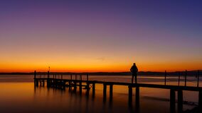 Free A Man Silhouette Standing On Wooden Pier Lonely At The Sea With Beautiful Sunset. Lsunset Seascape At A Wooden Jetty. Stock Photos - 173122703
