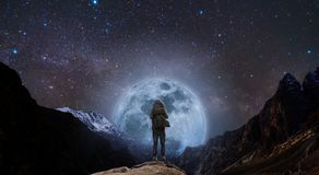 Free A Man With Backpack Standing On Mountain Peak At Night, And Silhouette Mountain With Bright Full Moon And Sky Full Of Stars Royalty Free Stock Photos - 118204528