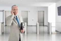 Free A Mature Businessman Talking On His Cell Phone In A Modern Office Building Lobby. Horizontal Format With Copy Space Stock Image - 175123471