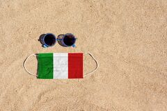 Free A Medical Mask In The Color Of The Italian Flag Lies On The Sandy Beach Next To The Glasses. Royalty Free Stock Photo - 209562785