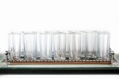 Free A Metal Tray With A Large Number Of Clear Glass Glasses Stands On A Glass Table. White Background Royalty Free Stock Photo - 173729405