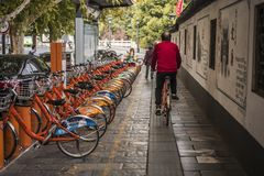 Free A Middle-aged Man In A Red Shirt Rides A Shared Bicycle Through A Shared Bicycle Parking Spot Royalty Free Stock Images - 131276539