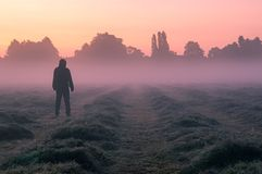 Free A Mysterious Hooded, Figure Standing In A Field On A Beautiful Early Misty Morning, Looking At The Sunrise Royalty Free Stock Image - 155543686
