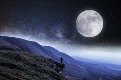 Free A Nightime Edit. A Hiker On The Edge Of A Cliff Surrounded By Mountains With The Moon And Stars Above Stock Images - 147168084