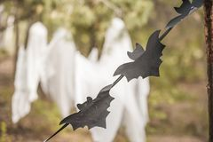 Free A Photo Project For Halloween In Nature. A Garland Of Black Drawn Bats Against The Backdrop Of Three White Ghosts In A Forest Of G Royalty Free Stock Image - 127595136