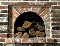 A Pile Of Logs Are Stacked Inside An Opening In A Brick Fireplace Wall F Royalty Free Stock Image