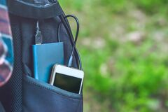 Free A Power Bank Charges A Smartphone In A Pocket Of A Black Backpack, On A Background Of Grass Royalty Free Stock Photography - 169804137