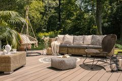 Free A Rattan Patio Set Including A Sofa, A Table And A Chair On A Wooden Deck In The Sunny Garden. Royalty Free Stock Images - 125026639