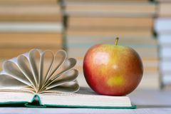 Free A Red Apple And An Open Book, The Pages Of The Book Are Gathered In A Fan For Beauty Royalty Free Stock Image - 120894896