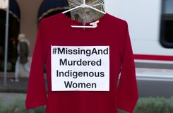 Free A Red Dress With Text `Missing And Murdered Indigenous Women` Is Hanging On The Tree. Royalty Free Stock Image - 178796826