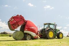 A Round Baler Discharges A Hay Bale During Harvesting Stock Image