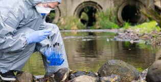 Free A Scientist In A Protective Suit And Mask, Collects A Sample Of Water In Test Tubes, Against The Background Of Drain Pipes, There Royalty Free Stock Image - 173688596