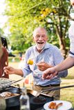 A Senior Man Standing By The Grill, Holding Corn On A Barbecue Party. Stock Images