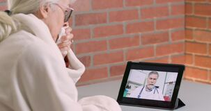 Free A Sick Senior Citizen Engaged In A Virtual Visit With Her Doctor Using Telehealth Stock Photography - 184744822