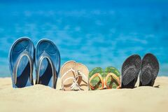 A Slippers Of The Whole Family In The Sand By The Sea On Nature While Traveling. Rest By The Water On Vacation With Shoes Royalty Free Stock Photos