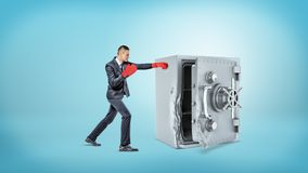 Free A Small Businessman Wears Red Boxing Gloves And Hits A Large Broken Metal Safe. Stock Images - 107347744