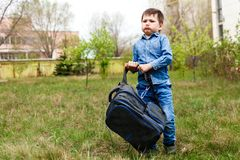 A Small Child Picks Up A Huge Heavy Backpack On The Green Grass Stock Images
