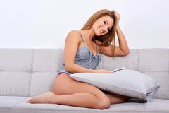 Free A Smiling Woman Sitting On A Sofa And Using Her Smartphone Stock Photography - 137842252