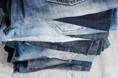 Free A Stack Of Carelessly Folded Woman`s Jeans On Gray Background. Close-up Of Jeans In Different Colors. Selective Focus Royalty Free Stock Photos - 159009468