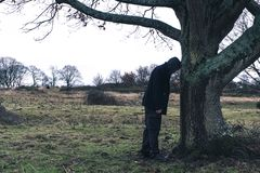 Free A Strange Surreal Picture Of A Mysterious Hooded Man Learning Against A Tree On A Bleak Moody Winters Day In The Countryside Stock Image - 166630421