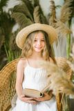 A Sweet Little Girl With Long Blond Hair In A White Sarafan And A Straw Hat In A Rattan Chair Stock Images