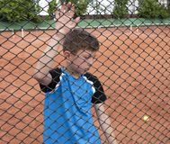 Free A Tearful Sad Boy Child Tennis Player Stands Behind A Metal Fence And Looks Downcast Dejectedly. Losing Emotion In Sport Royalty Free Stock Photo - 167053575