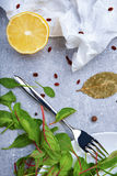A Top View Of Cut Lemon On A Grease-proof Paper Next To A Tableware. Dinner Composition On A Gray Background. Stock Photo