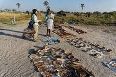 A Tourists Buys Some Souvenirs At A Village Basket Market, Okavango Delta, Botswana, Africa Royalty Free Stock Images