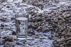Free A Transparent Glass Of Pure Natural Cold Water Stands On A Rock In A Mountain Stream. Royalty Free Stock Photography - 162850037