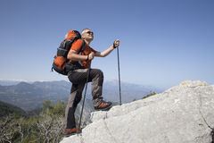 A Traveler Stands On Top Of A Mountain And Looks Out To Sea. Stock Photo