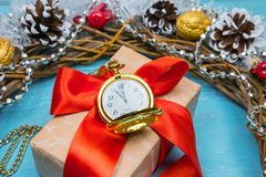 A Vintage Clock In The Snow Against A Background Of A Gift And A Christmas Wreath Stock Photo