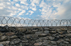 A Wall Of Grey Stone Topped With Barbed Wire. Stock Images