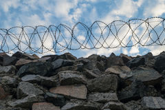 A Wall Of Grey Stone Topped With Barbed Wire. Royalty Free Stock Image