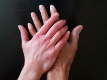 A White And Black Hand, Old And Young, Holding Eachother Royalty Free Stock Photography