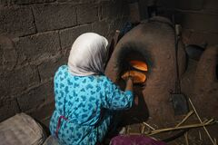 Free A Woman Baking Traditional Moroccan Bread In A Clay Oven, At Her Home In A Traditional Village In The Draa-Tafilalet Region, Moroc Stock Photo - 211563500