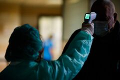 Free A Woman In A Protective Suit Measures The Temperature Of A Man Inside The Henri Coanda International Airport For Coronavirus Royalty Free Stock Image - 174457906