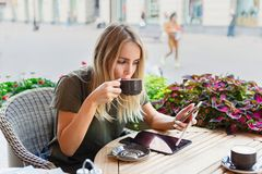 Free A Woman With Smiley Face Holding And Using Ipad Tablet Pc While Drinking Coffee In Modern Cafe Royalty Free Stock Images - 159067039
