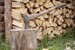 Free A Woodcutter`s Metal Axe With A Wooden Handle Is Stuck In A Log For Chopping Wood Against The Background Of A Split Tree Stacked Stock Photos - 183333473