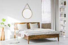 Free A Wooden Rustic Bed Frame And A Home Library Bookcase In A Natural, Sunlit Hotel Room Interior With White Walls Royalty Free Stock Images - 120479489